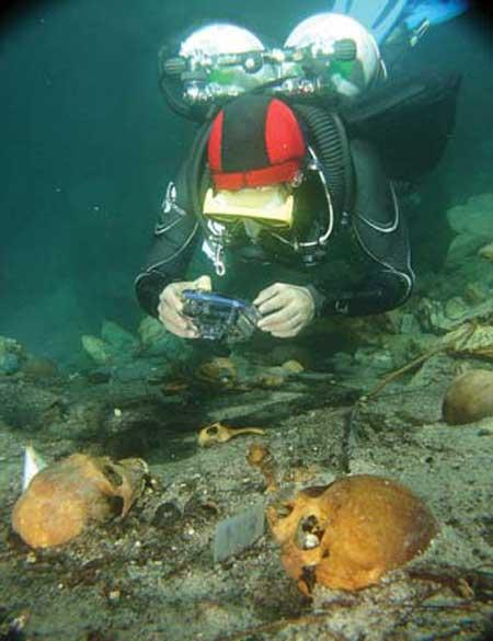buzo fotografiando unos cráneos en un Cenote